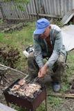 Uomo senior che cucina pesce gatto Fotografia Stock