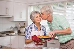 Uomo senior che dà alla sua moglie un bacio mentre prendendo muffin Fotografia Stock