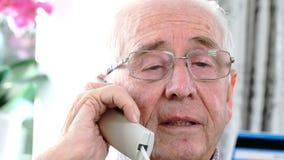 Uomo senior che dà credito i dettagli della carta sul telefono video d archivio