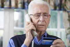 Uomo senior che dà credito i dettagli della carta sul telefono Fotografie Stock Libere da Diritti