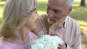 Uomo senior che dà i fiori alla donna cara, sorpresa piacevole della data, anniversario fotografie stock