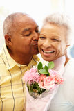 Uomo senior che dà i fiori alla moglie fotografie stock