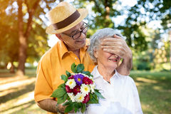 Uomo senior che dà mazzo dei fiori colorati alla sua moglie fotografia stock