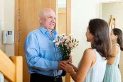 Uomo senior che dà mazzo di fiori alla donna Immagine Stock