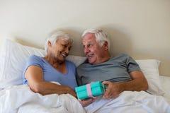 Uomo senior che dà un regalo di sorpresa alla donna nella camera da letto Immagine Stock