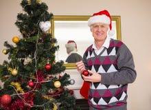 Uomo senior che decora l'albero di Natale Immagine Stock