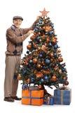 Uomo senior che decora un albero di Natale fotografie stock