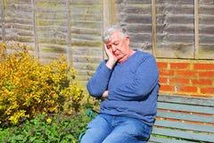 Uomo senior che dorme fuori su un banco Fotografie Stock
