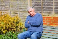 Uomo senior che dorme fuori su un banco Immagini Stock