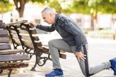 Uomo senior che fa allungando allenamento su un banco di parco Immagini Stock Libere da Diritti