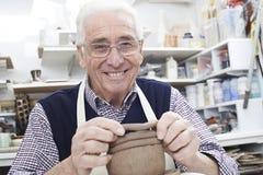 Uomo senior che fa il vaso della bobina nello studio delle terraglie fotografia stock
