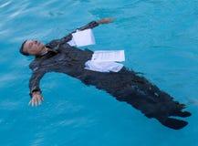 Uomo senior che galleggia fra le carte in acqua fotografia stock libera da diritti