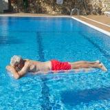 Uomo senior che galleggia sull'acqua Immagine Stock