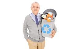 Uomo senior che giudica un recipiente di riciclaggio pieno di vecchia roba Fotografia Stock