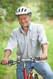Uomo senior che gode del giro del ciclo nella campagna immagine stock