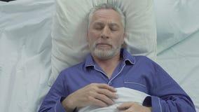 Uomo senior che gode della comodità di sonno dovuto il materasso ed i cuscini ortopedici archivi video