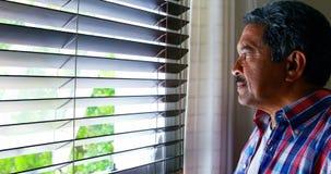 Uomo senior che guarda attraverso la finestra mentre mangiando caffè 4k stock footage
