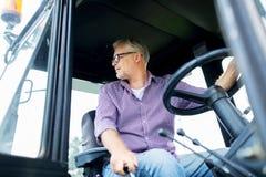 Uomo senior che guida trattore all'azienda agricola Immagine Stock
