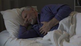 Uomo senior che ha attacco di cuore, dolore toracico tagliente di sofferenza mentre dormendo archivi video