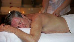 Uomo senior che ha massaggio in stazione termale stock footage