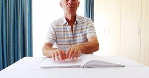 Uomo senior che legge un libro di Braille stock footage