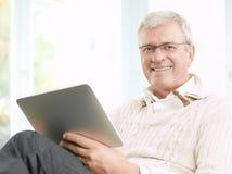 Uomo senior che legge un libro elettronico Fotografia Stock