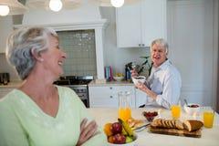 Uomo senior che mangia prima colazione e che interagisce con la donna senior Fotografia Stock Libera da Diritti