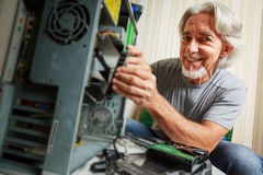 Uomo senior che monta un desktop computer Fotografie Stock