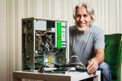 Uomo senior che monta un desktop computer Fotografia Stock