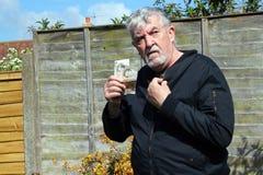 Uomo senior che nasconde i suoi soldi Fotografie Stock Libere da Diritti