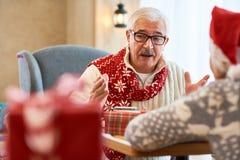 Uomo senior che parla con sua moglie alla cena di Natale fotografie stock