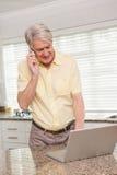 Uomo senior che per mezzo del suo computer portatile sul telefono Fotografia Stock