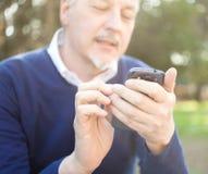 Uomo senior che per mezzo del suo telefono cellulare Fotografia Stock