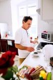 Uomo senior che prepara caffè Mettendo zucchero in tazze Immagini Stock Libere da Diritti