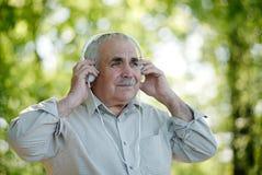 Uomo senior che si concentra sulla sua musica Immagine Stock
