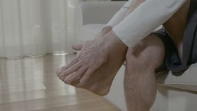Uomo senior che si rilassa e che massaggia il suo piede stanco a casa che si siede sullo strato stock footage