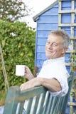 Uomo senior che si rilassa nel giardino con la tazza di caffè Immagine Stock Libera da Diritti