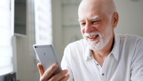 Uomo senior che si siede a casa con lo smartphone Parlando facendo uso del messaggero mobile app Mano d'ondeggiamento sorridente archivi video