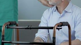 Uomo senior che si siede davanti alla struttura di camminata, infermiere che mette mano sulla sua spalla video d archivio