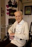 Uomo senior che si siede nella sedia a rotelle nella struttura di assistenza Immagine Stock