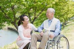 Uomo senior che si siede su una sedia a rotelle con il badante Immagine Stock