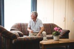 Uomo senior che si siede su uno strato Immagini Stock Libere da Diritti