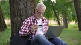 Uomo senior che si siede sull'erba e sui biglietti di prenotazione online, maschio che riposa nel parco archivi video