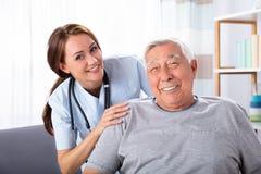 Uomo senior che si siede sulla sedia a rotelle con l'infermiere femminile fotografie stock