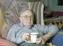 Uomo senior che si siede sullo strato con la tazza bevente Fotografia Stock