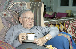 Uomo senior che si siede sullo strato con la tazza bevente Immagine Stock Libera da Diritti