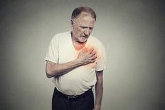 Uomo senior che soffre dal cattivo dolore nel suo attacco di cuore del petto Immagini Stock Libere da Diritti