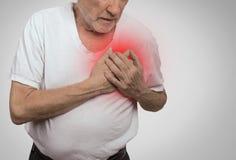 Uomo senior che soffre dal cattivo dolore nel suo petto Immagini Stock