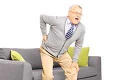 Uomo senior che soffre dal dolore alla schiena Fotografie Stock