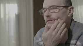 Uomo senior che soffre dal forte dolore di dente che sfrega il suo cheeck che ritiene cattivo - stock footage